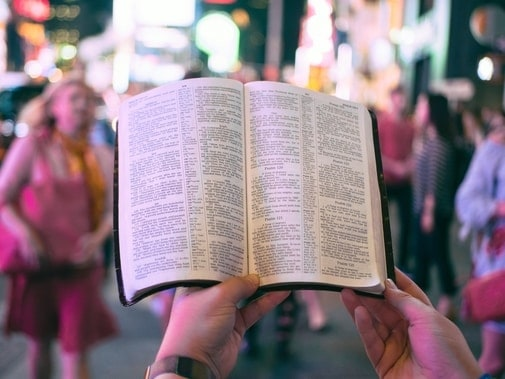 man reading the bible in a crowd of people